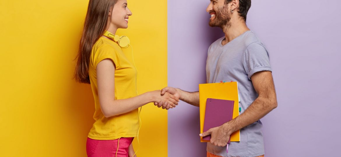 Happy groupmates meet after holidays, shake hands, agree to work together as team, stand in profile, lovely woman with headphones meets friend. Unshaven young man holds notepad talks with female
